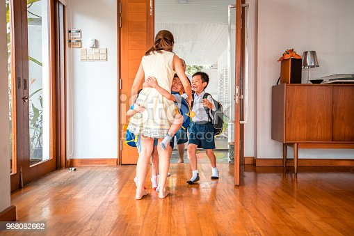 670900812istockphoto Mother embracing her children when coming home 968062662