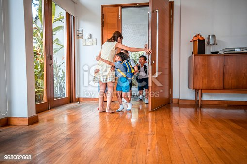 670900812istockphoto Mother embracing her children when coming home 968062668