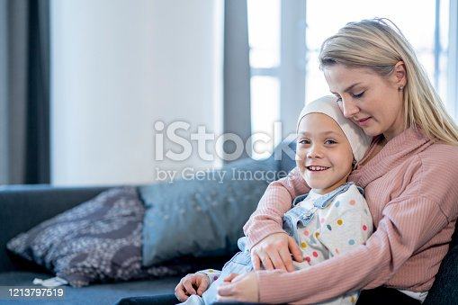 A young Mother sits on a sofa at home, with her young daughter on her lap, between cancer treatments.  She is hugging her tightly as they enjoy a close moment together.  The little girl is dressed casually, has a head scarf on and is smiling.