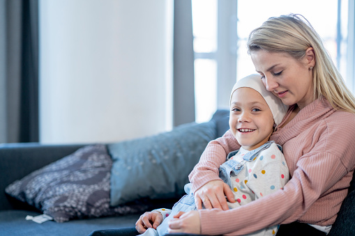 Mother Embracing Her Daughter with Cancer stock photo