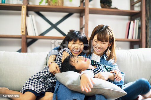 172407626istockphoto Mother embracing son and daughter on sofa. 542555886