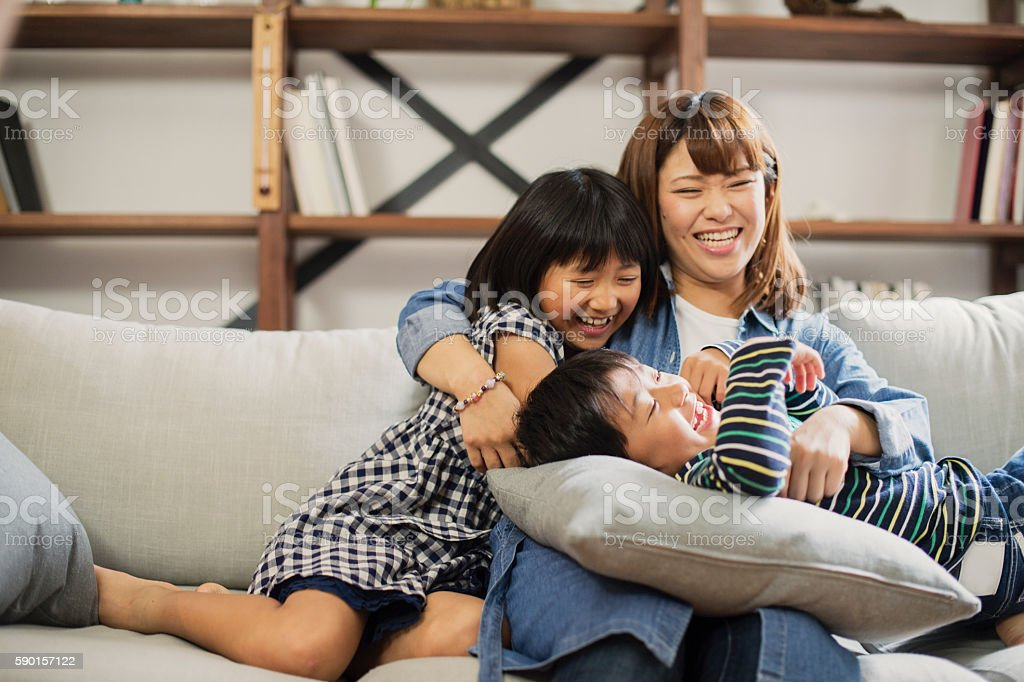 Mother embracing son and daughter on sofa. stock photo