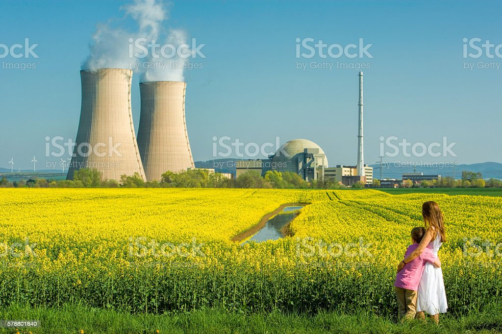 Mother embracing Son in Front of Nuclear power station stock photo