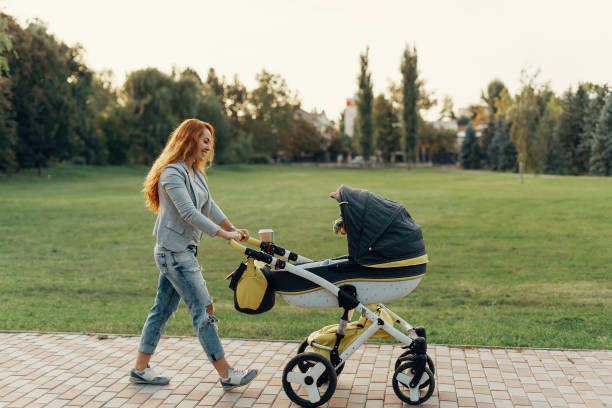 Mother enjoying walk carrying her little child in his baby trolley. A young mother enjoying the park walk with her little child relaxing in his baby trolley. baby stroller stock pictures, royalty-free photos & images