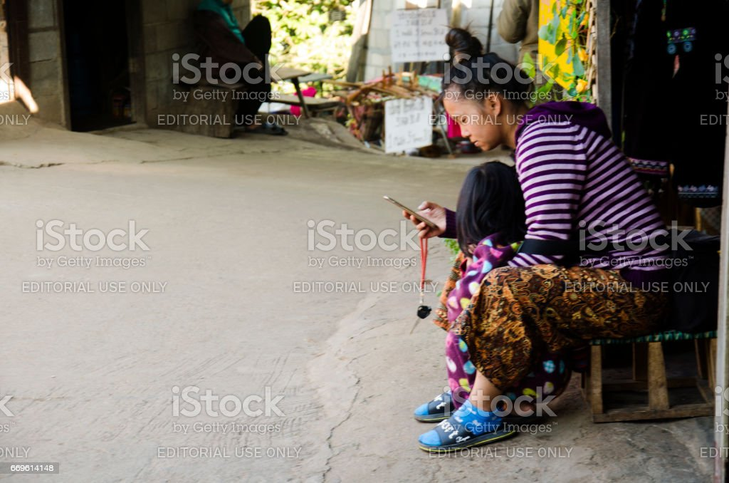Mother Ethnic Hmong parenting child and playing mobile at house stock photo