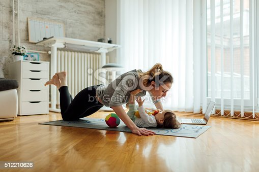 istock Mother Exercise With Her Baby At Home 512210626