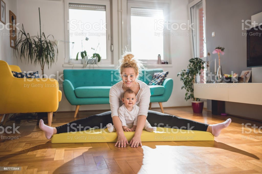 Mother Exercise With Her Baby At Home stock photo