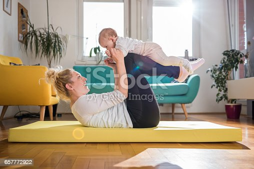 istock Mother Exercise With Her Baby At Home 657772922