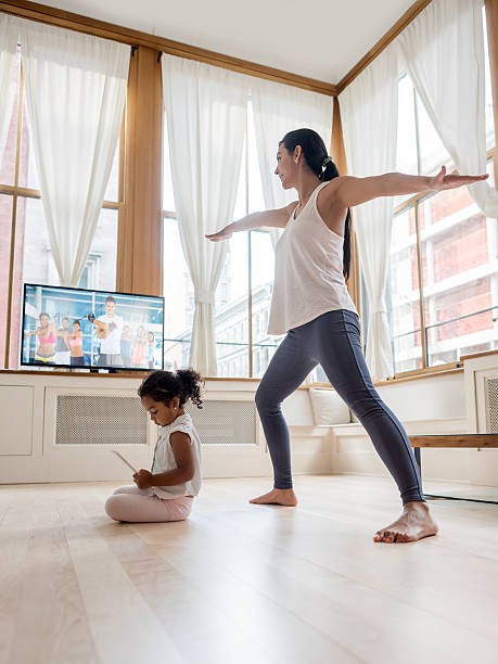 mother exercising at home - yoga videos stock-fotos und bilder