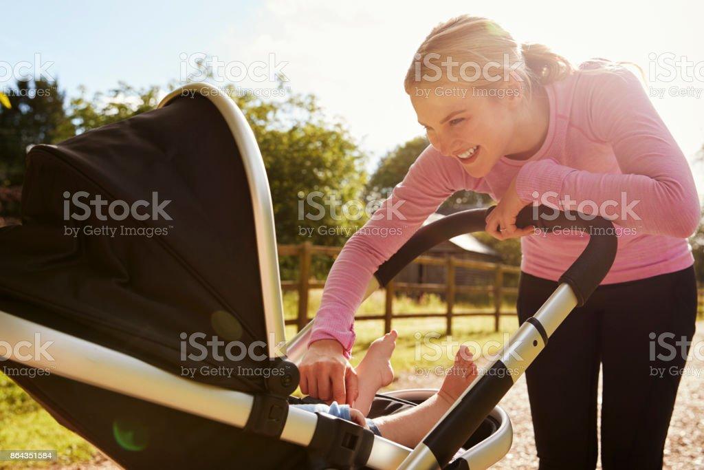 Ejercicio ejecutando mientras empuja el cochecito de bebé de la madre - foto de stock