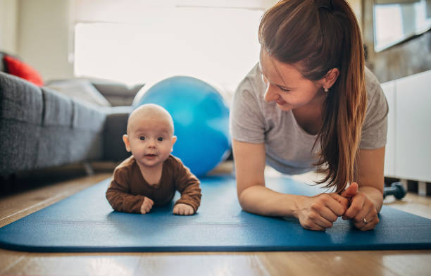 Mother exercising with her baby son at home stock photo