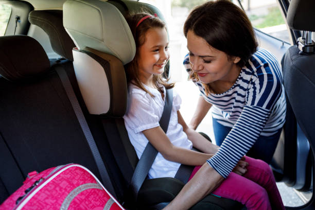 Mother fastening child safety seat belt in car stock photo