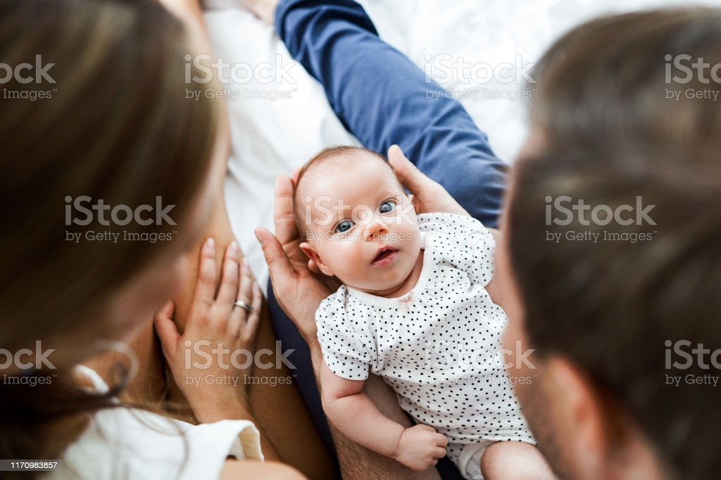Mother ,father and baby child on a white bed playing Mother father and baby child on a white bed 0-1 Months Stock Photo