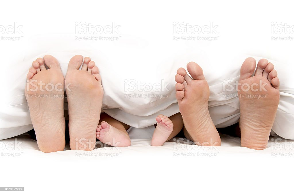 Mother Father and Baby Feet under Blanket stock photo