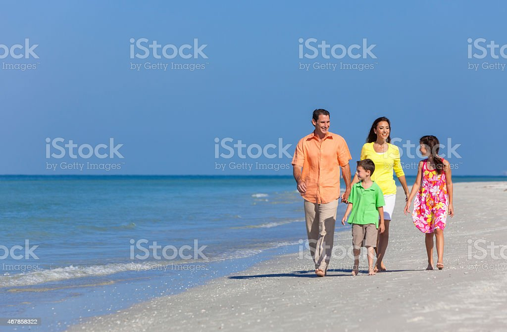 Mother Father and Children Family Walking On Beach stock photo