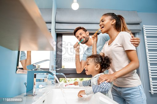 Concept of mixed race family. Low angle view of cheerful young adult man hugging happy woman and brushing teeth at morning. Father and mother standing together with african daughter in bathroom