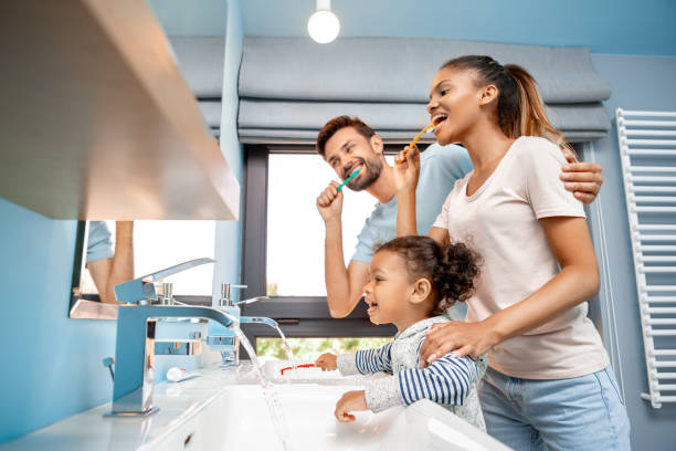 Mother, father and daughter brushing teeth in bathroom Concept of mixed race family. Low angle view of cheerful young adult man hugging happy woman and brushing teeth at morning. Father and mother standing together with african daughter in bathroom dental health stock pictures, royalty-free photos & images