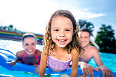 Young mother and father with their daughter sitting on pool lilo in swimming pool in aqua park. Summer heat and water.