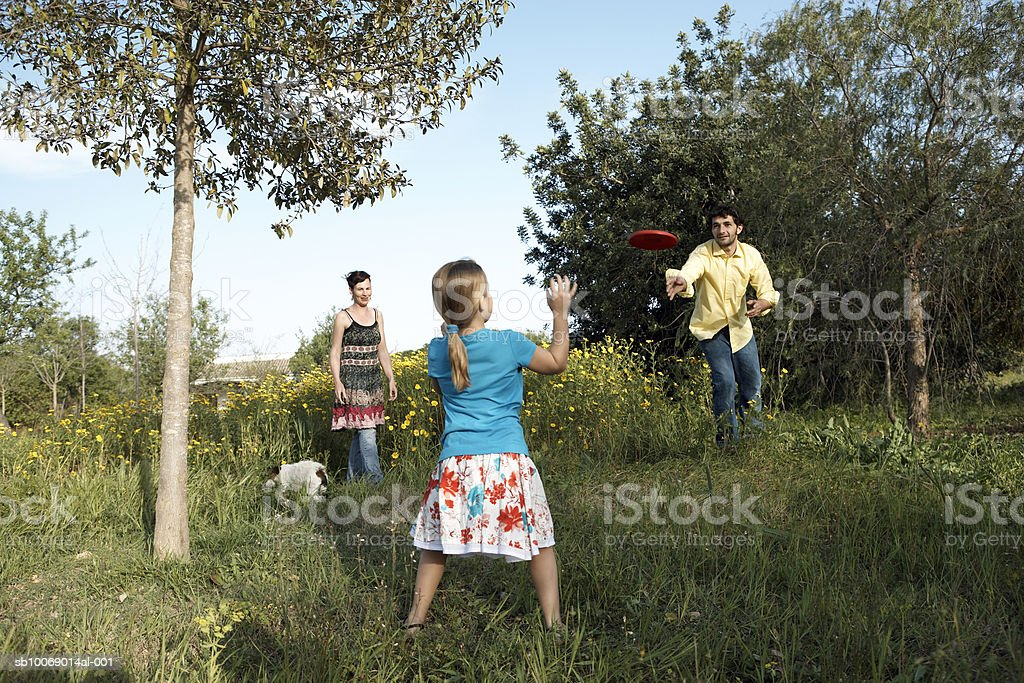 Mother, father and daughter (8-9) playing with frisbee in garden royalty-free stock photo