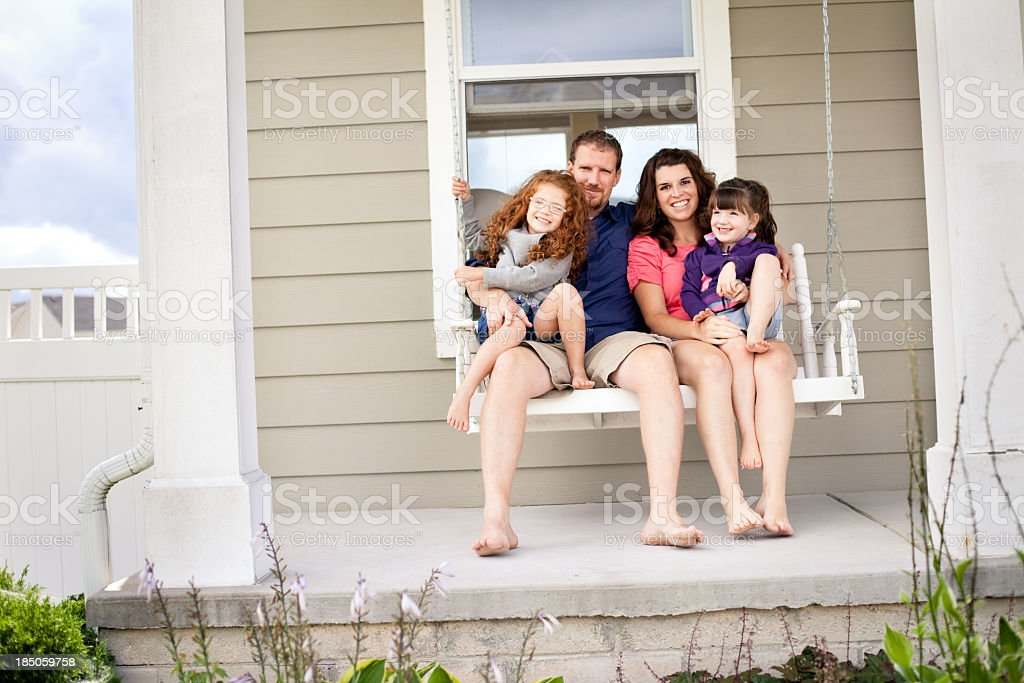Mother Father And Daughters Sitting On Porch Swing