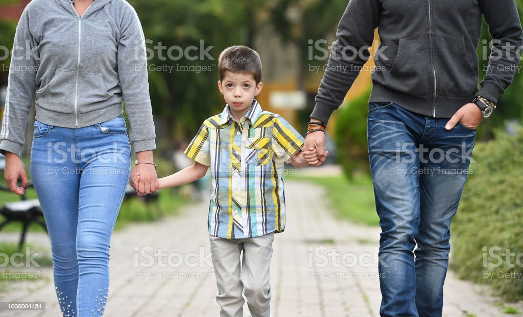 mother, father and son holding hands in parkmother, father and son...