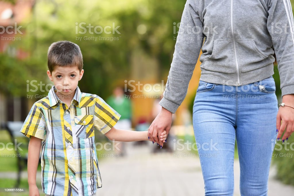 mother and son holding hand in a parkmother and son holding hand in a...