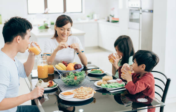 Mother, father and two children eating together stock photo