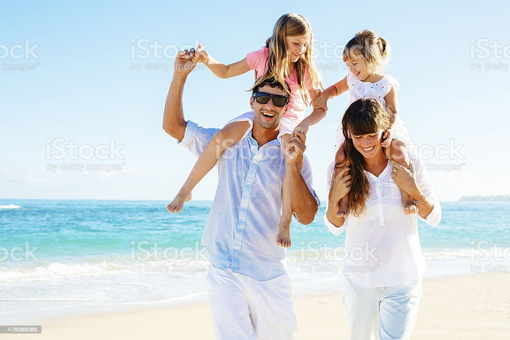Mother, father and two kids having fun on a beach stock photo