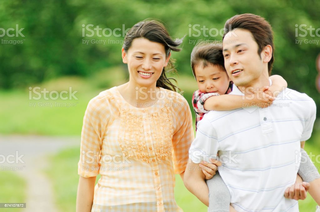 Mother father daughter a piggyback ride as near to walk royalty-free stock photo
