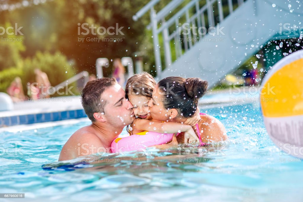 Mother, father kissing daughter in swimming pool. Sunny summer. stock photo