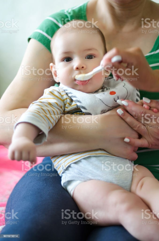 Mother feeding baby, baby infant eating from spoon stock photo