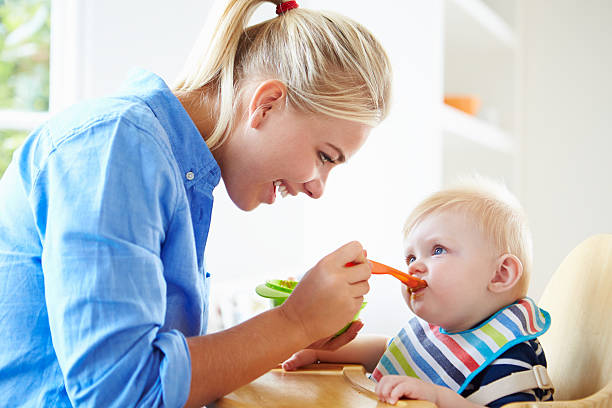 Mother Feeding Baby Boy In High Chair stock photo