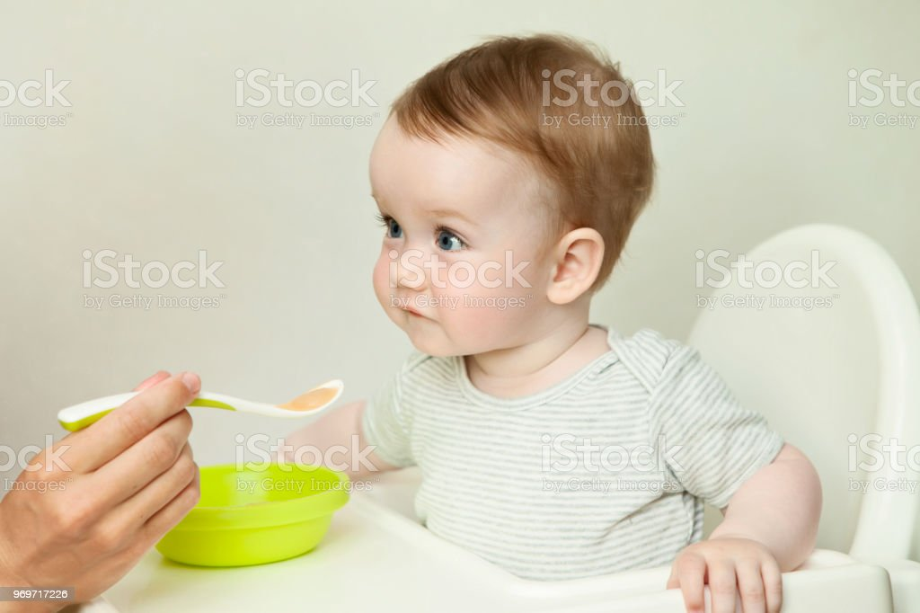 mother feeding baby boy with a spoon stock photo