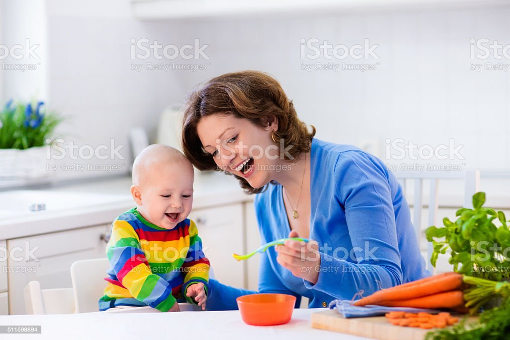 Mother feeding baby first solid food stock photo
