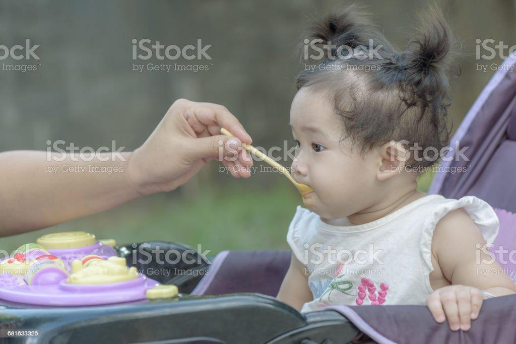 Mother feeding baby girl with porridge. stock photo