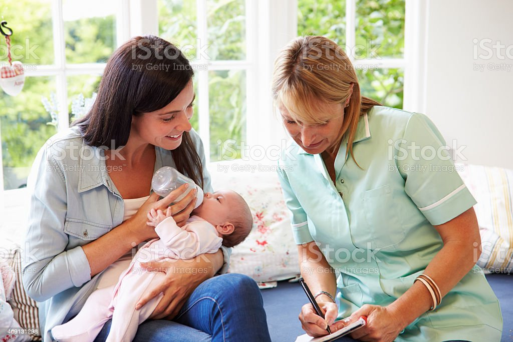 Mother feeding baby meeting with in-home health visitor stock photo
