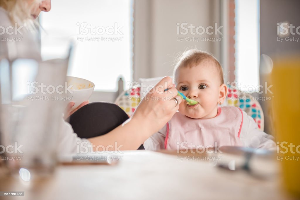 Mother feeding baby - foto de acervo