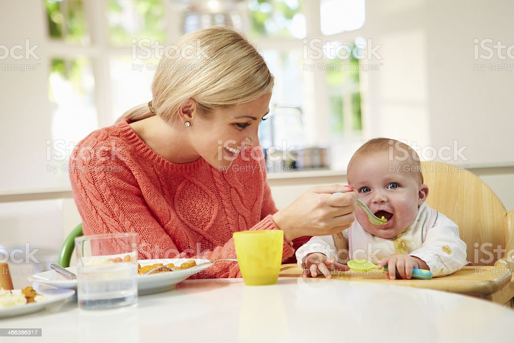 Mother Feeding Baby Sitting In High Chair At Mealtime stock photo