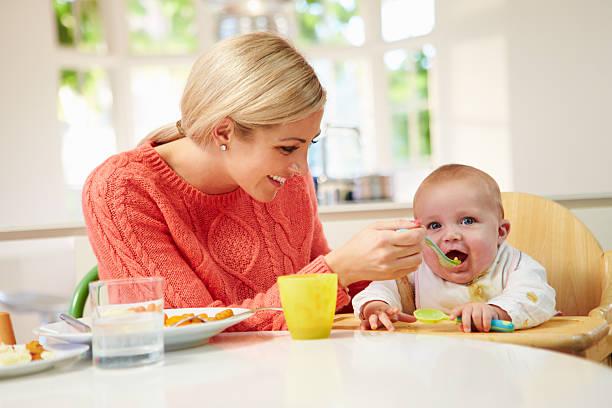 mutter fütterung baby im hochstuhl sitzen bei den - kinderstuhl und tisch stock-fotos und bilder