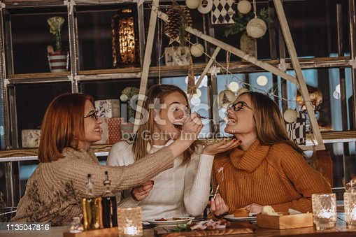 Mature woman is feeding her daughters with an appetizer in a restaurant.