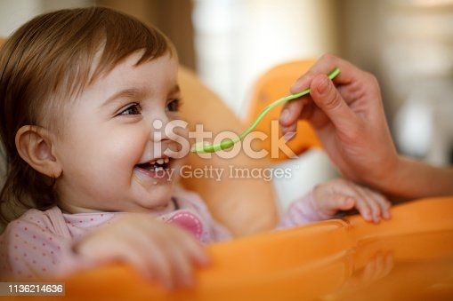 Mother feeding happy toddler girl with a spoon