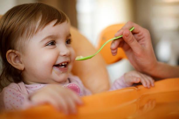 Mutter füttert glückliches Kleinkind mit einem Löffel – Foto
