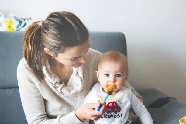 mother, feeding her baby boy with mashed pumpking - mash food state stock photos and pictures