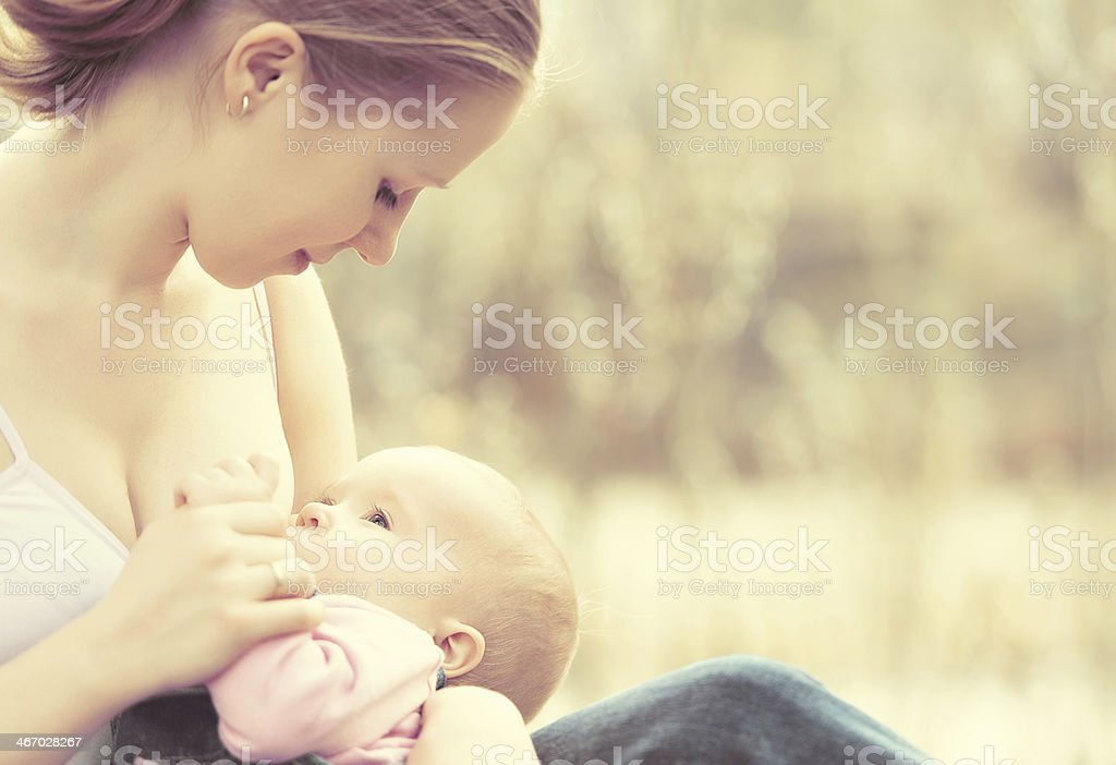 mother feeding her baby in nature outdoors stock photo