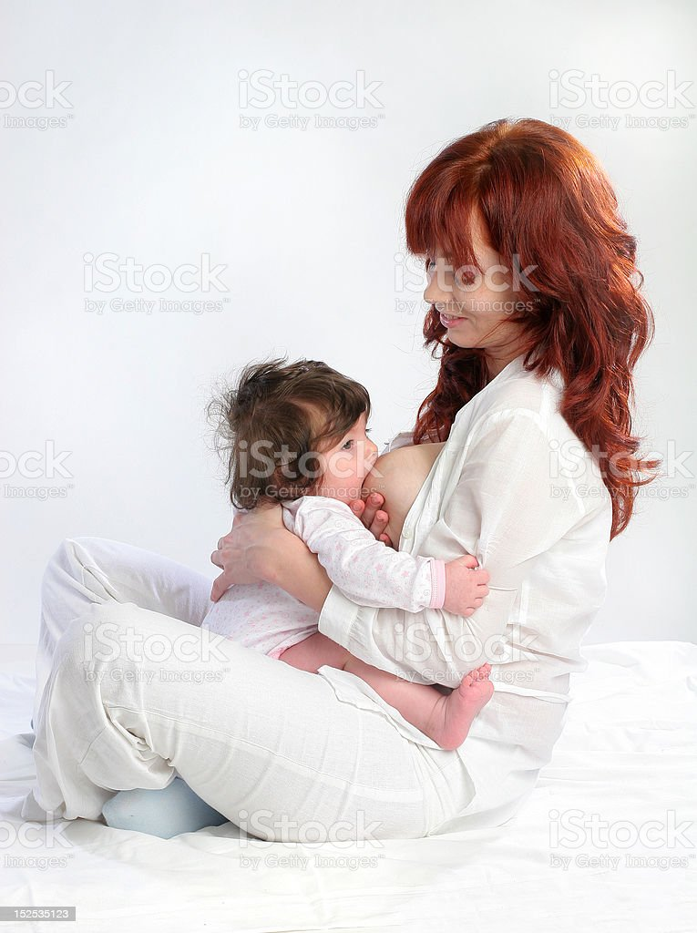Mother feeding her baby. Sitting belly-to-belly stock photo