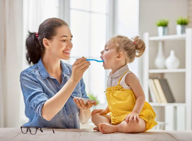 Mãe alimentando seu filho - foto de acervo