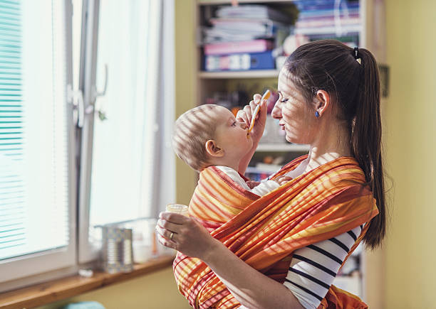 Mother feeding her daughter stock photo
