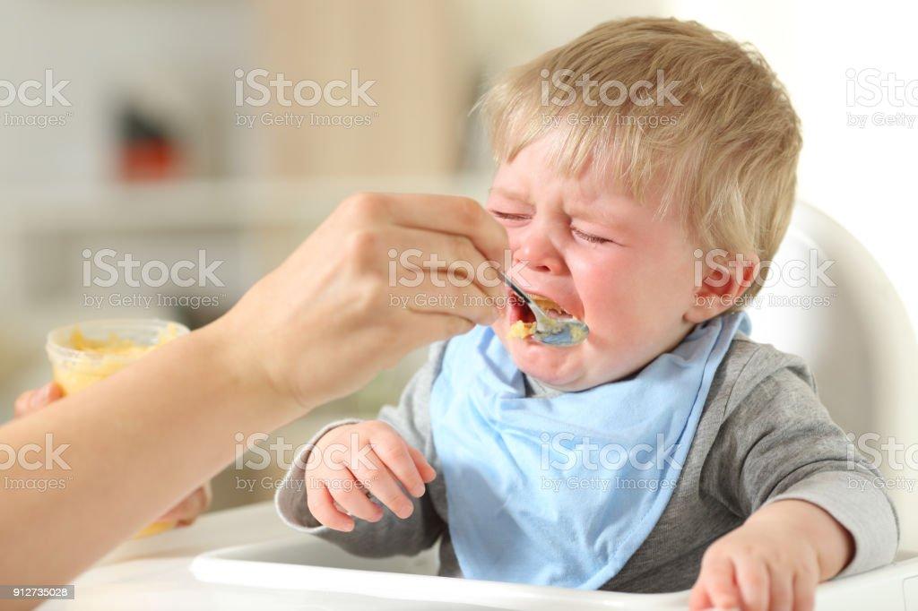 Mãe alimentando seu filho que está chorando - foto de acervo