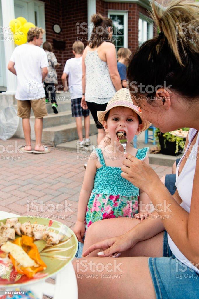 Mother feeding little girl on family gathering. stock photo