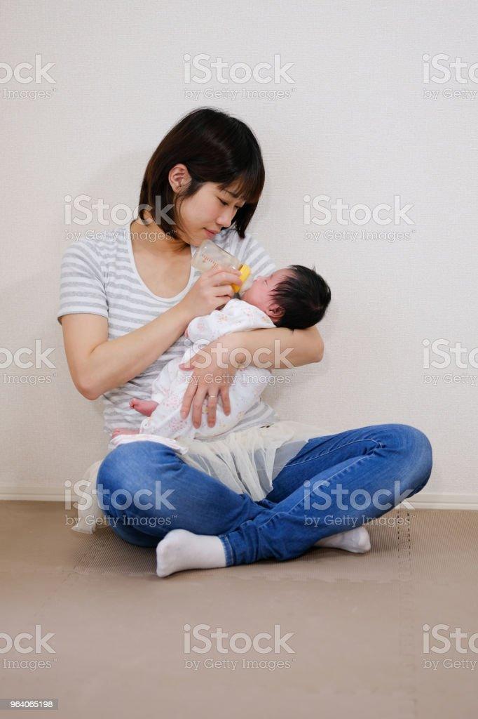 お母さんが赤ちゃんにミルクを供給 - 1歳未満のロイヤリティフリーストックフォト